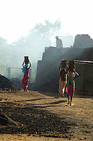 These women carry some 12 bricks each on a small construction site on the road from Mumbai to Goa about 3 hours from Mumbai,India,the brick furnace is near by hence the dust and smoke