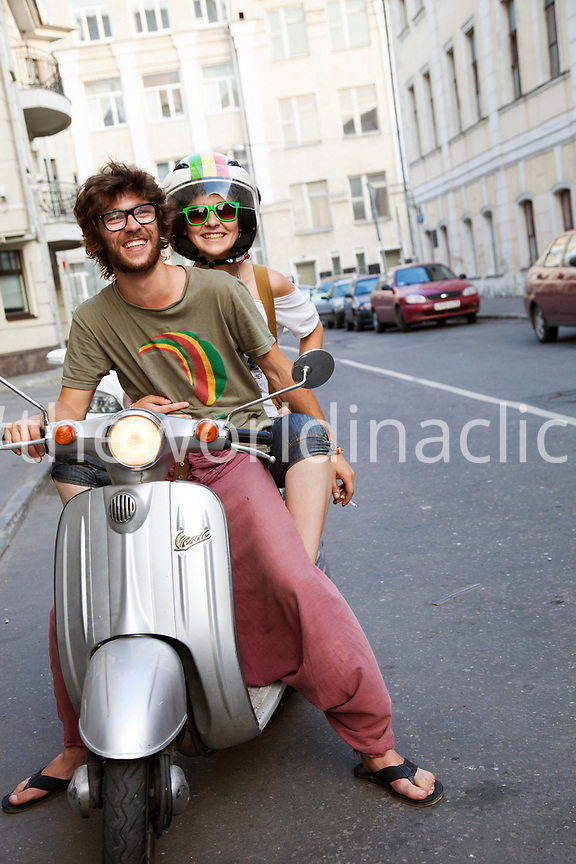 RUSSIA, Moscow. A young Muscovite couple on a Vespa.