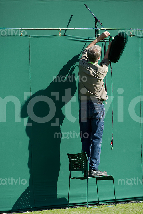 A technican sets up a microphone on a court. The Wimbledon Championships 2010 The All England Lawn Tennis & Croquet Club  Day 1 Monday 21/06/2010