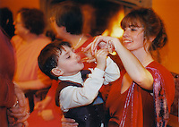 A young boy trying champagne from his mother's glass during a wedding reception.