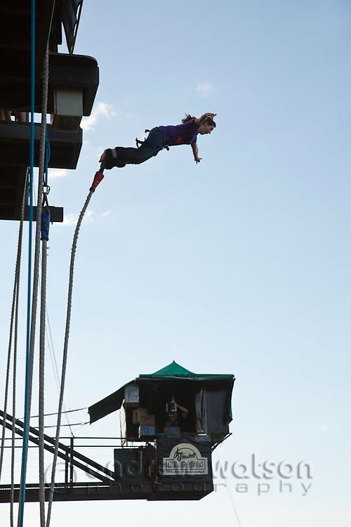 Woman leaping from AJ Hackett bungy tower.  Smithfield, Cairns, Queensland, Australia