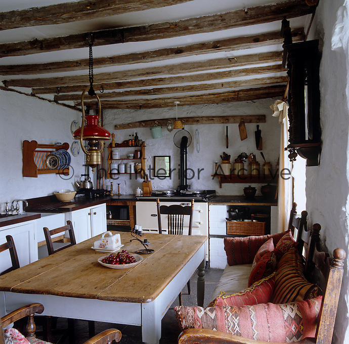 A brass oil lamp hangs from the beamed ceiling above the table in this rustic kitchen