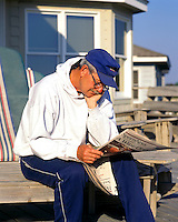 Retired man relaxing and reading the newspaper.