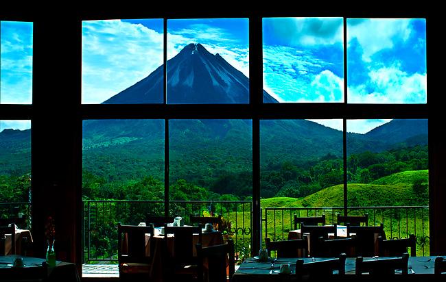 Mountain lodge restaurant windows provide dramatic views of the Arenal Volcano in El Castillo, Costa Rica.