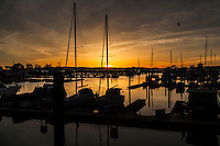 The sun, behind the sailboat mast, creates a sunburst.  Sunset at San Leandro Marina on San Francisco Bay.