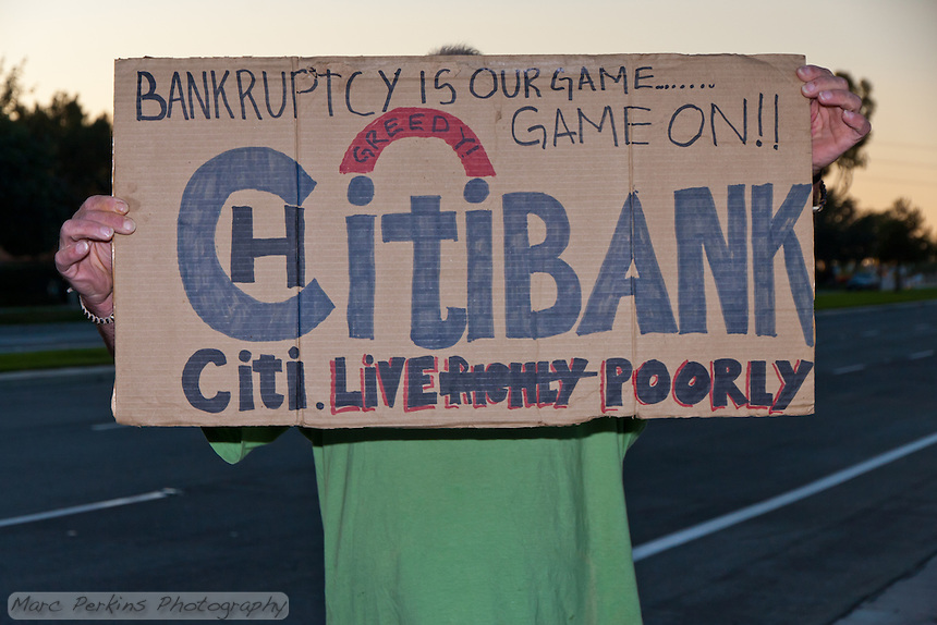 """A man holds a sign reading """"Citibank - Bankruptcy is our game … game on!! Citi. Live -Richly- Poorly"""" at the Occupy Orange County - Irvine camp."""