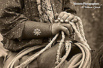 A sepia toned photograph of a cowboys hands, cuffs, rope and saddle. Cowboy Photos, riding,roping,horseback