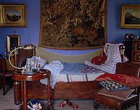 An Empire bed in the living room doubles as a sofa during the day has its bedcover removed in preparation for a siesta