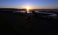 Swansea, UK. Saturday 21 June 2014<br /> Pictured: Two cyclists ride on the Swansea Bay cycle path near Mumbles as the sun rises over the city marking the Summer Solstice and the year's longest day.