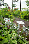 white painted metal garden chairs and a table sit in a hidden lookout spot of a waterside woodland garden surrounded by lush summer woodland gardens including hostas, crocosmia, and yellow irises