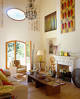 Artwork and hand-painted panels adorn the upper sections of the walls of the double-height living room