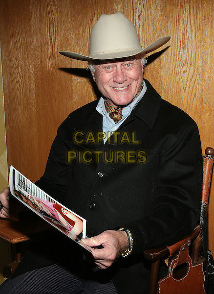 LARRY HAGMAN.2010 Chiller Theatre Expo Toy, Model and Film Expo held at the Hilton Hotel Parsippany,  New Jersey, Parsippany, New Jersey, USA..October 30th, 2010.half length beige stetson hat black jacket coat sitting chair.CAP/ADM/PZ.©Paul Zimmerman/AdMedia/Capital Pictures.