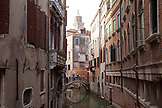 ITALY, Venice.  View of homes and bridge over a canal.