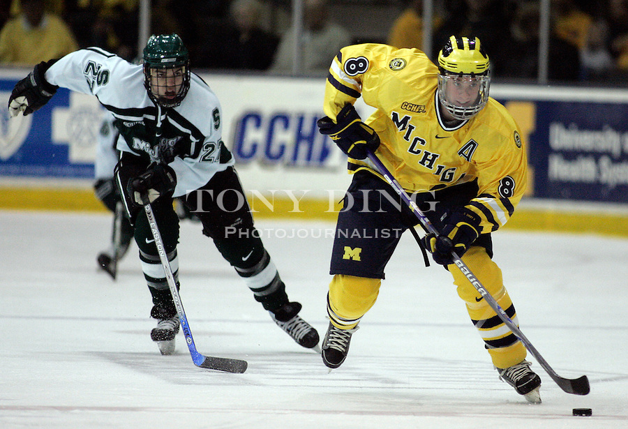4 November 2006: Michigan senior defender Jason Dest (8) dribbles the puck, followed by MSU forward Daniel Sturges (27), during a CCHA conference ice hockey game between Michigan and in-state rival Michigan State, at Yost Ice Arena in Ann Arbor, MI. Michigan won the game 6-2.