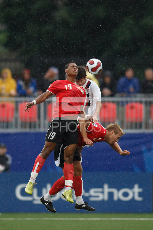 Austria forward (19) Rubin Okotie and defender (2) Thomas Panny battle USA defender (5) Nathan Sturgis for a header. Austria (AUT) defeated the United States (USA) 2-1 in overtime of a FIFA U-20 World Cup quarter-final match at the National Soccer Stadium at Exhibition Place, Toronto, Ontario, Canada, on July 14, 2007.