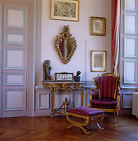 A 19th century French gilt-framed armchair with a matching footstool stands next to a Louis XIV console table in the Music Room
