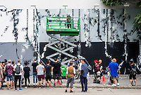 New York, NY 12 September 2015 -  Passersby pause to warch Futura (aka Lenny McGurr, Futura 2000) create his street art at the Bowery Mural