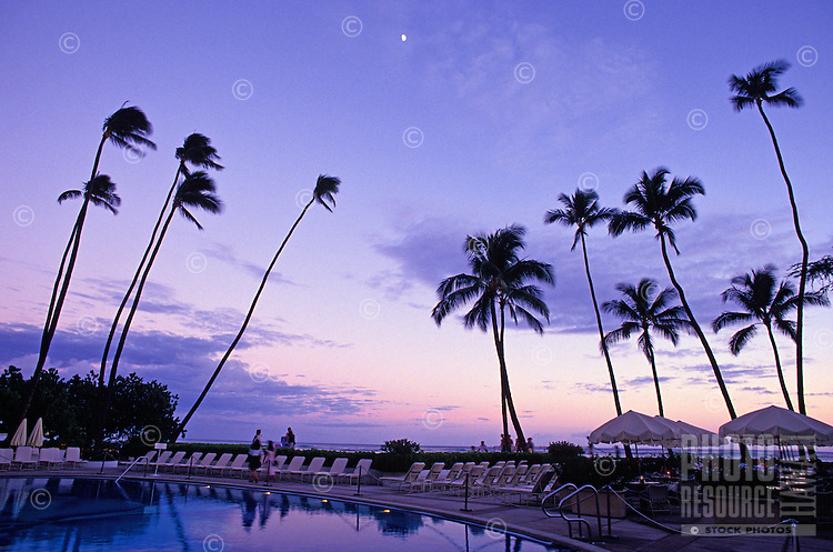 Pool area at the Halekulani Hotel in Waikiki, at dusk