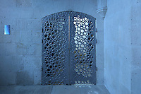Aluminium doors with design of circles by Ste Baney, leading from the chapel to the staircase of the bell tower, in St Thibaud's Chapel, themed as the Lapidary, in Le Tresor de la Cathedral d'Angouleme, in Angouleme Cathedral, or the Cathedrale Saint-Pierre d'Angouleme, Angouleme, Charente, France. The 12th century Romanesque cathedral was largely reworked by Paul Abadie in 1852-75. In 2008, Jean-Michel Othoniel was commissioned by DRAC Aquitaine - Limousin - Poitou-Charentes to display the Treasure of the Cathedral in some of its rooms, which opened to the public on 30th September 2016. Picture by Manuel Cohen. L'autorisation de reproduire cette oeuvre doit etre demandee aupres de l'ADAGP/Permission to reproduce this work of art must be obtained from DACS.