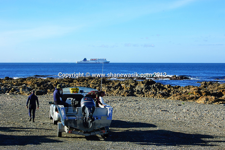 Divers prepare their boat in the car park whilst the interislander ferry passes on the way to Picton in the distance,