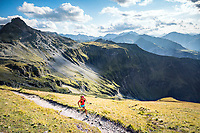 A woman trail runner running uphill with poles while doing a trail from Weisstanenntal to the Pizol, Switzerland