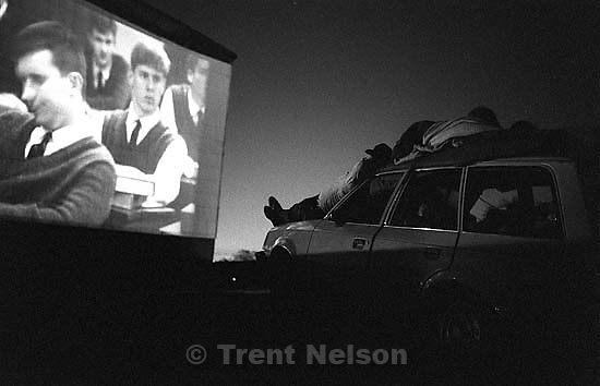 People watching movie on car at Timp Drive-In theater.<br />