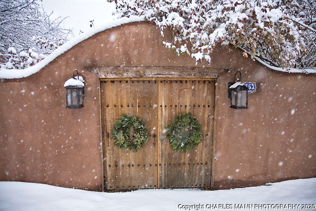 Snow festoons a gate and adobe wall during a snowfall on a winter's day in Santa Fe.