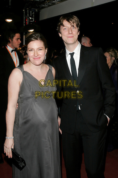 KELLY McDONALD & DOUGIE PAYNE.The Orange British Academy Film Awards in 2008 The Royal Opera House, Covent Garden, London, England. .February 10th, 2008 .BAFTA Arts half length dress grey gray suit couple pregnant .CAP/AH.©Adam Houghton/Capital Pictures