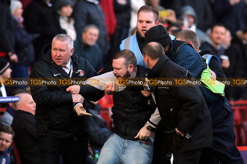 A Charlton protestor is escorted out of the ground by security staff and stewards during Charlton Athletic vs Middlesbrough, Sky Bet Championship Football at The Valley on 13th March 2016