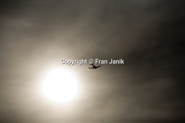 Just after take off from the island  of Martha's Vineyard, a small twin engine low wing aircraft flys west along South beach. The plane is silloutted  against a monochromatic diffused sun and sky.