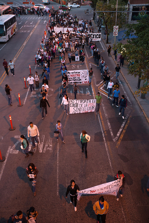 Caravan for Ayotzinapa and demonstrators hold posters and placards during a march in protest for the disappearance of 43 students from Ayotzinapa's teacher training college, in Guadalajara, Jalisco, Mexico on November 18, 2014. The parents and relatives of the 43 missing students still do not believe the official line that the young men are all dead, and with classmates, social organizations and human rights defenders, they started on Thursday a national caravan. They split up into three different caravans, branching out to share information face to face with supporters in other cities and rally nationwide support. The three groups will meet in Mexico City on Thursday 20 for a general strike and massive marches to demand justice and fight against corrupted government and organized crime. Criticism of the government has intensified in Mexico, and many are demanding that the search for the 43 missing students continue until there is concrete evidence to the contrary. (Photo by Bénédicte Desrus)