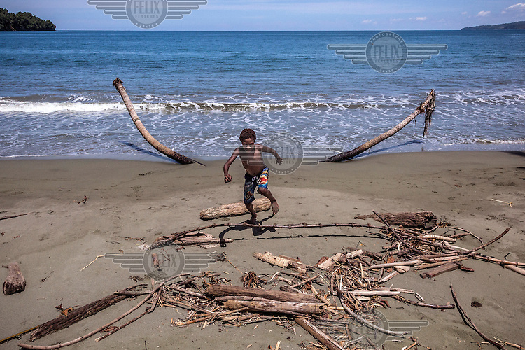 A boy plays on a shore near the scattered remains of some coconut palms.