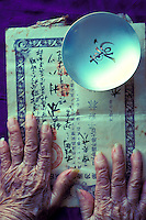 The hands of a hundred year old Japanese woman touch her original passport from the time of her immigration from Japan to Hawaii in 1907