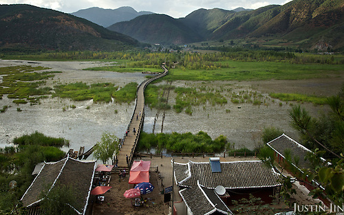 """The """"Marriage Bridge"""" at the legendary Lugu Hu Lake in Sichuan Province, southwestern China. Tradition has brides crossing the bridge on the back of the man. This is a newly constructed bridge, replacing the old one, whose remnants are seen on the right."""