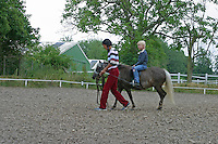 Shetland-Pony, Shetlandpony, Shetty, Shetti, Ponyhof, Shetland - Pony wird eingeritten, Kind, Mädchen sitzt im Sattel, Reitlehrerin führt das Pony am Halfter auf dem Reitplatz, Reiten