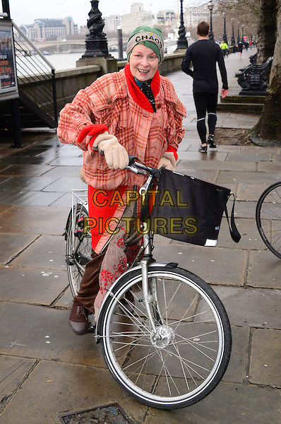 LONDON, ENGLAND - JANUARY 15: Dame Vivienne Westwood leaves on her bike after attending anti-fracking press conference.  Fashion designer joins Prisca Merz, volunteer director of End of Ecocide in Europe, at a joint press conference to explain the environmental damage caused by controversial shale gas 'fracking' technology as proposed by multi-national company Total on HMS President, Victoria Embankment, on January 15, 2014, in London, England.<br /> CAP/JOR<br /> &copy;Nils Jorgensen/Capital Pictures
