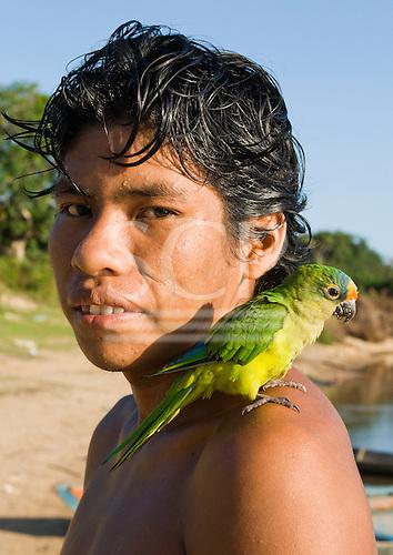 Pará State, Brazil. Iriri River. Aldeia Kararaô (Kayapo). Briti Kayapo with pet parrot.