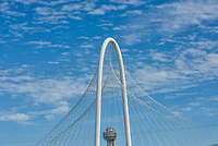 Reunion Tower and the top of the Margaret Hunt Hill Bridge in downtown Dallas during the day with nice clouds with a blue sky.