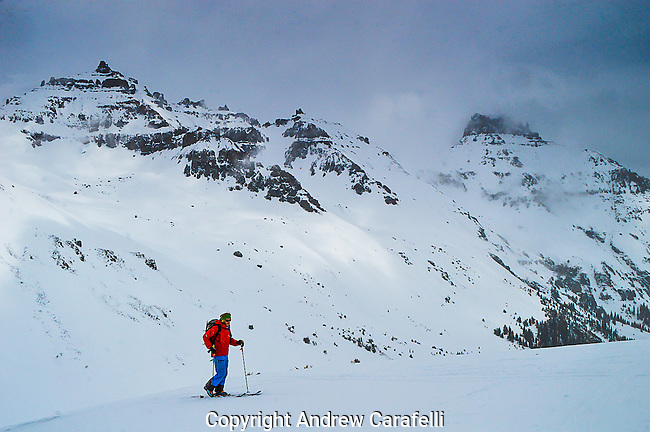 A backcountry skier, surrounded by 13,000 foot peaks of the San Juan Mountains, skins up into Yankee Boy Basin near Ouray, Colorado.