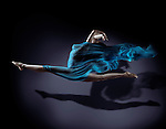 Beautiful young woman dancer in splits in mid-air with flowy blue cloth around her naked body and her shadow on dark background