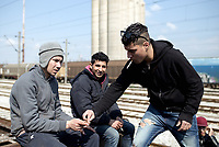 Pictured: Three migrants at the OSE freight depot in Thessaloniki, Greece. Wednesday 05 April 2017<br /> Re: A year after an agreement was signed between Greece and Turkey for the management of refugees. Migrants, mostly from Morocco, Algeria and Tunisia, have been living in disused train carriages at the Thessaloniki freight depot of OSE in northern Greece, the company managing the railways in the country. Some of the migrants climb onto moving trains, or even hide themselves in storage areas, hoping that they will cross the border.