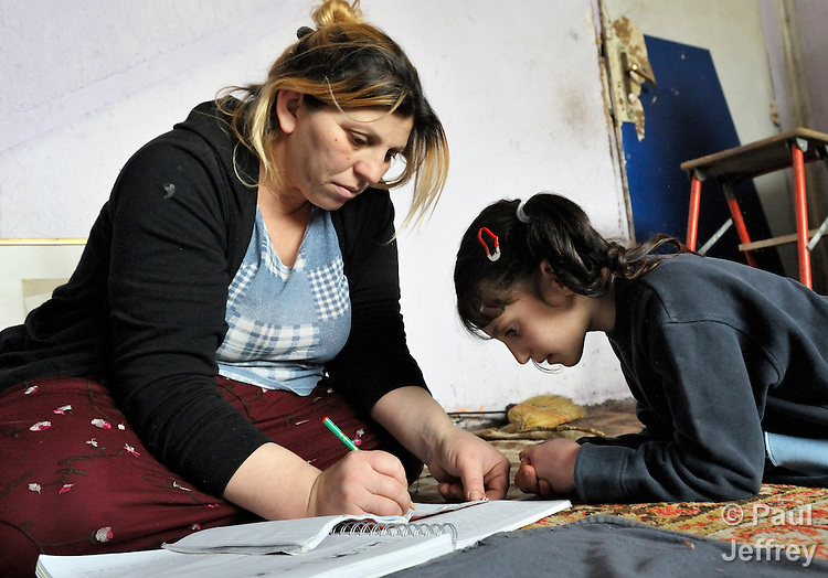 Giltena Duda studies for her basic literacy class in her home in the Zemun Polje Roma neighborhood of Belgrade, Serbia, while her daughter Djemieja looks on. Ms. Duda is pregnant with her seventh child. She and her husband are Roma refugees from Kosovo, and thus legally marginalized in Serbia. They built their home on unregistered land and pirate their electrical hookup. Without legal residency, their children can't attend a regular school, and they have difficulties getting formal employment. Yet both adults participate in a literacy program sponsored by the Branko Pesic School, where their children attend classes. The school is supported by Church World Service.