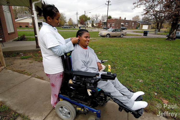 Diane Lopez gets her hair fixed by a home visitor from the Lessie Bates Davis Neighborhood House.