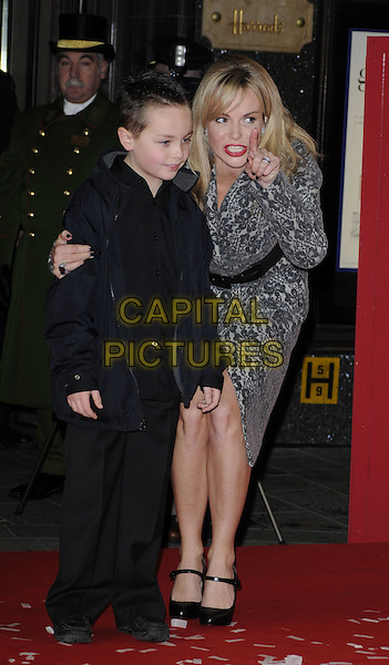 AMANDA HOLDEN with Adam Wheeler (8).opens Harrods Winter Sale, wearing a wool coat by Catherine Melandrino..Knightsbridge, London, England, UK,.26th December 2009..full length grey gray pattern print wrap black waist belt  collar mary janes shoes bending leaning boy child finger gesture hand .CAP/CAN.©Can Nguyen/Capital Pictures.
