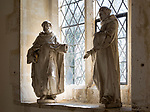 Two statues of monks or saints standing by a window inside village parish church at Dauntsey, Wiltshire, England, UK