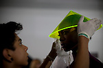 An assistant places a plastic conical Asian-influenced hat on a model before hitting the runway, backstage for the Brazilian brand, Neon, at São Paulo Fashion Week for Summer Season 2013/2014, at Bienal, in São Paulo, Brazil, on Wednesday, March 20, 2013.