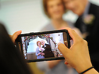 A staff member makes a picture of Wesley Enhanced Living Upper Moreland residents Dorothy Dickel, 83, and Bud Galow, 90, after they were married Saturday May 28, 2016 in Upper Moreland, Pennsylvania. It is the first wedding ever held at Wesley Enhanced Living. (Photo by William Thomas Cain)