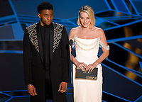 Chadwick Boseman, left, and Margot Robbie present the award for best adapted screenplay at the Oscars on Sunday, March 4, 2018, at the Dolby Theatre in Los Angeles. (Photo by Chris Pizzello/Invision/AP)