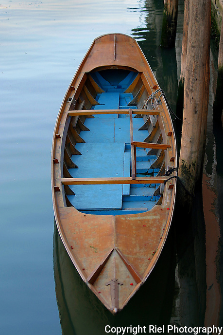 This blue bottomed boat is docked in the shade on a canal of Venice, Italy
