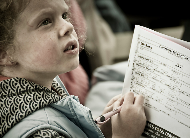 A young girl at the races pretending to read the racing form.